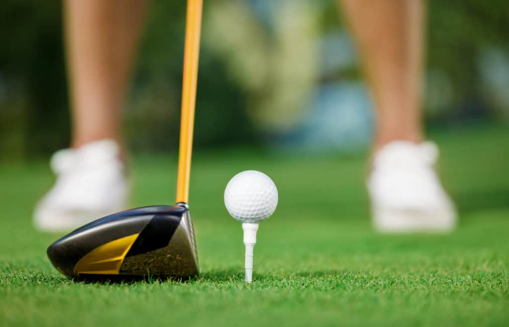 Golf ball and stick with golfer legs in background